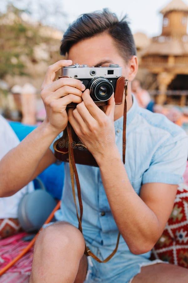 Portret trzyma retro kamerę i robi fotografii chłopiec z krótkim czarni włosy, podczas gdy siedzący w na otwartym powietrzu kawia fotografia stock