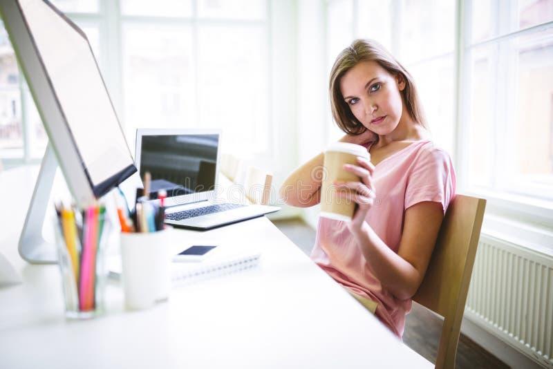 Portret trzyma rozporządzalną filiżankę zmęczony projektant grafik komputerowych zdjęcia royalty free