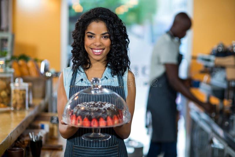 Portret trzyma tortowego stojaka z czekoladowym tortem uśmiechnięta kelnerka zdjęcia stock