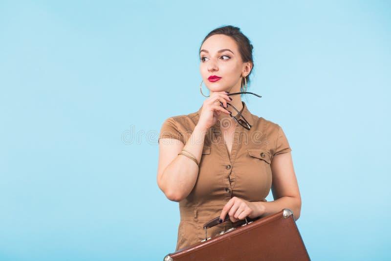 Portret trzyma walizkę odizolowywająca nad błękitnym tłem, podróżą, wakacjami i urlopowym pojęciem z podnieceniem młoda kobieta, zdjęcia stock
