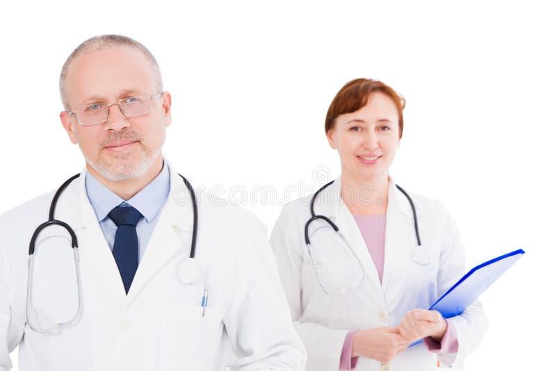 Portret twee glimlach artsen op witte achtergrond, medische verzekering, nadruk op mannelijke arts worden geïsoleerd die royalty-vrije stock afbeelding