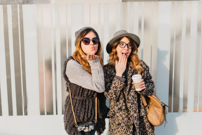 Portret twee modieuze grappige gelukkige meisjes die pret op straat in stad hebben Zonnige dag van het fashinable jonge vrouw rei stock afbeelding