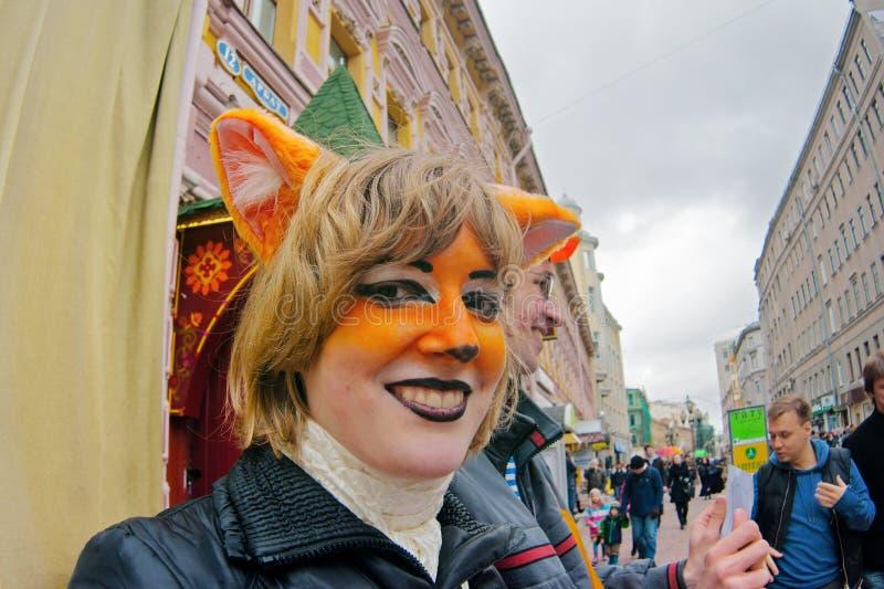 Portret uśmiechnięta młoda kobieta z twarz obrazu lisem wewnątrz i lisów ucho na flashmob na Arbat fotografia royalty free