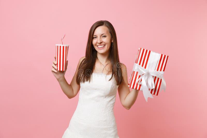 Portret uśmiechnięta piękna panny młodej kobieta w ślubnej sukni mienia czerwieni pudełku z prezentem, teraźniejsza plactic filiż zdjęcia royalty free