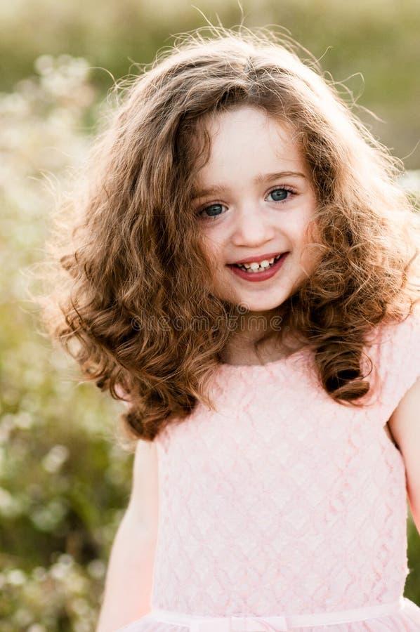 Portret uśmiechnięta powabna mała dziewczynka z kędzierzawym włosy zdjęcia stock