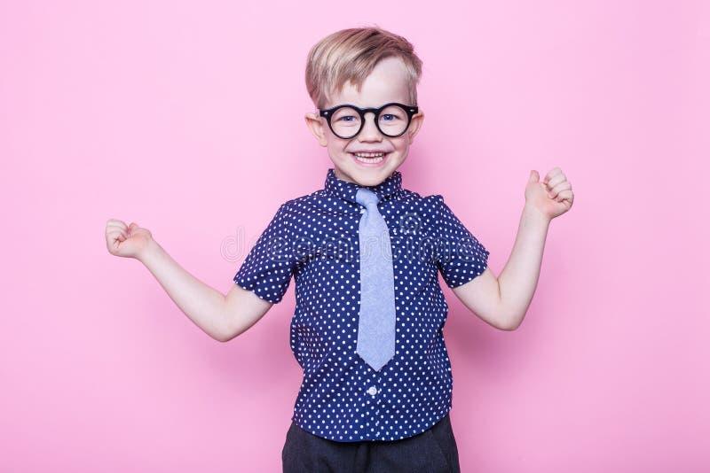 Portret uśmiechać się chłopiec w śmiesznym krawacie i szkłach troszkę szkoła preschool Moda Pracowniany portret nad różowym tłem zdjęcia stock
