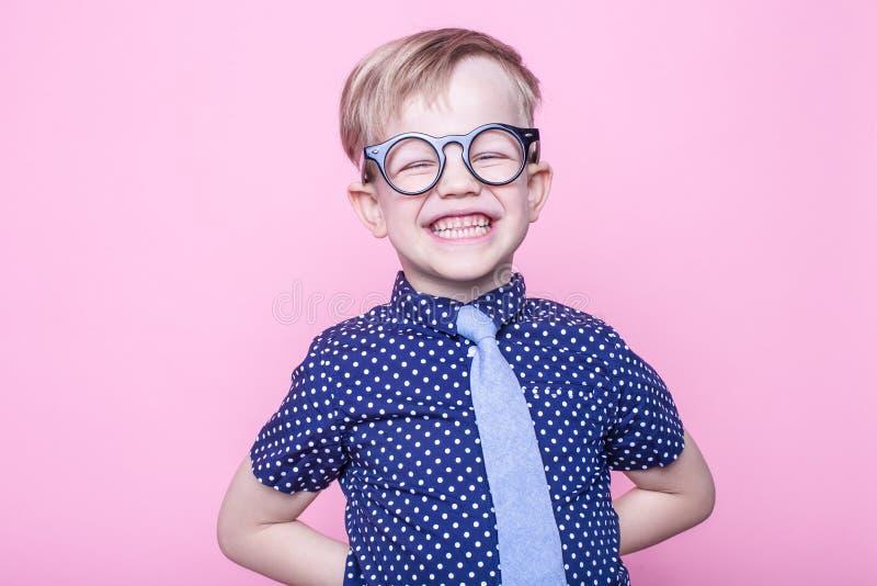Portret uśmiechać się chłopiec w śmiesznym krawacie i szkłach troszkę szkoła preschool Moda Pracowniany portret nad różowym tłem zdjęcia royalty free