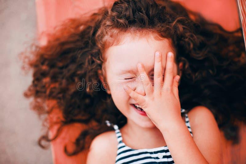 Portret uśmiechać się kędzierzawej śmiesznej dziewczyny w Żywym koralu obraz stock