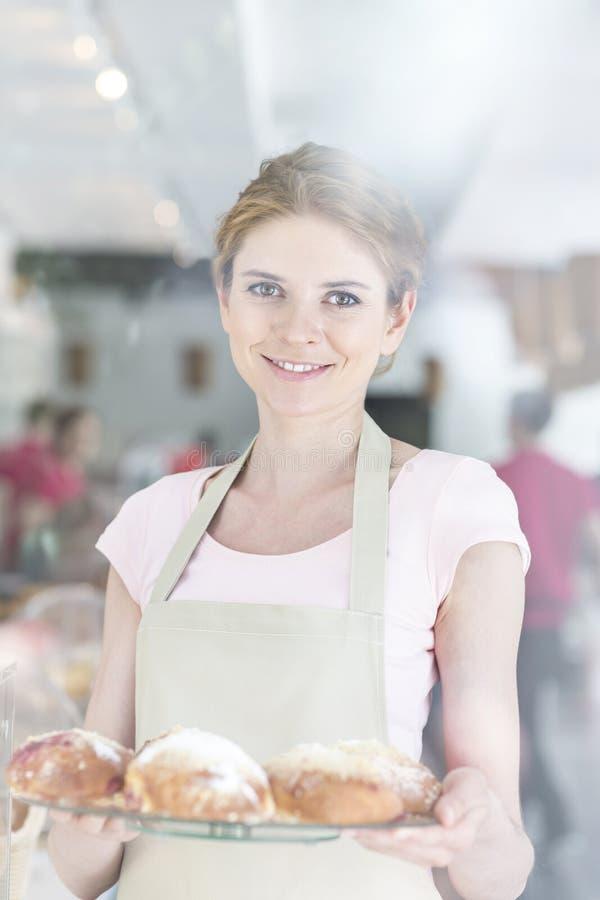 Portret uśmiechać się pięknej młodej kelnerki słuzyć świeżego chleb przy restauracją fotografia stock