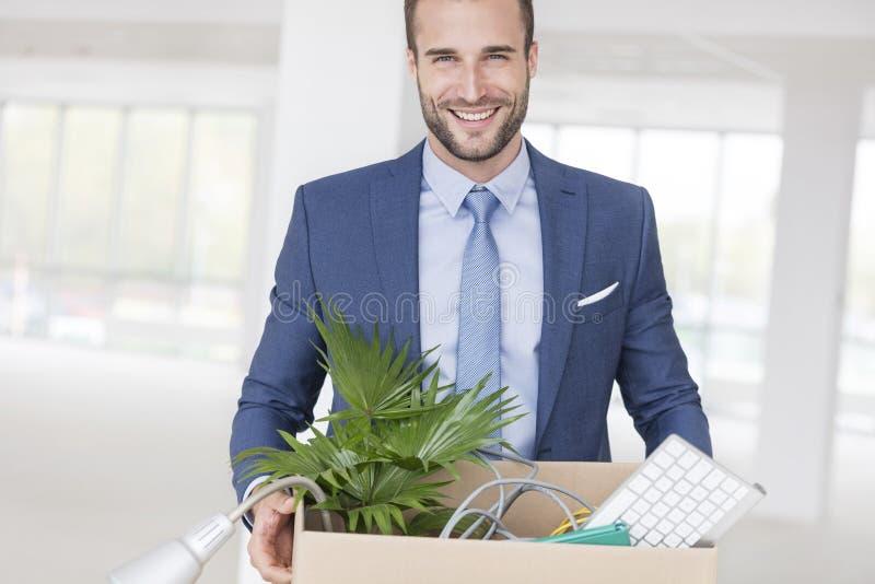 Portret uśmiechać się przystojną młodą biznesmen pozycję z kartonem w nowym biurze zdjęcie stock