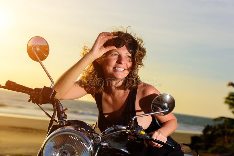 Portret uśmiecha się okulary przeciwsłonecznych na czole i trzyma piękny kobiety obsiadanie na motocyklu, obrazy stock