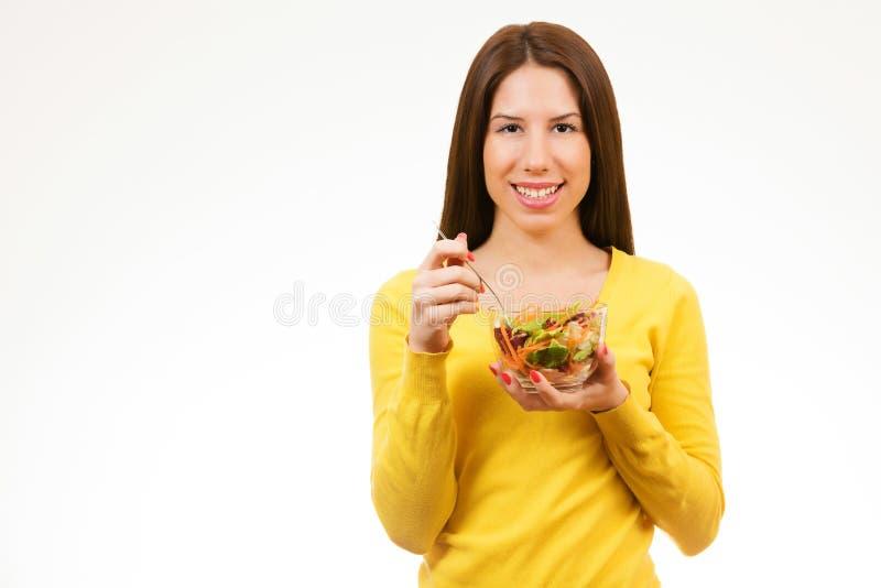 Portret uśmiecha się puchar sałatka i je młoda kobieta, obrazy stock