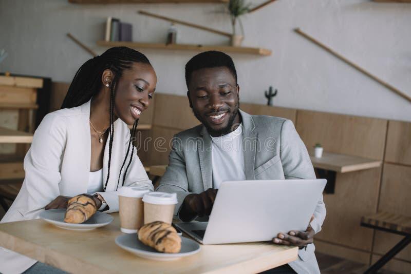 portret uśmiechnięci amerykanin afrykańskiego pochodzenia przyjaciele używa laptop wpólnie przy stołem zdjęcia royalty free