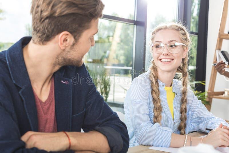 portret uśmiechnięci biznesowi koledzy ma rozmowę podczas gdy siedzący przy stołem fotografia stock