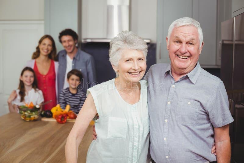 Portret uśmiechnięci dziadkowie z rodziną w kuchni zdjęcie stock