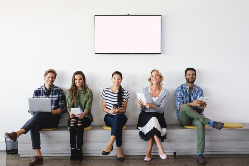 Portret uśmiechnięci ludzie biznesu siedzi na siedzeniu zdjęcie stock
