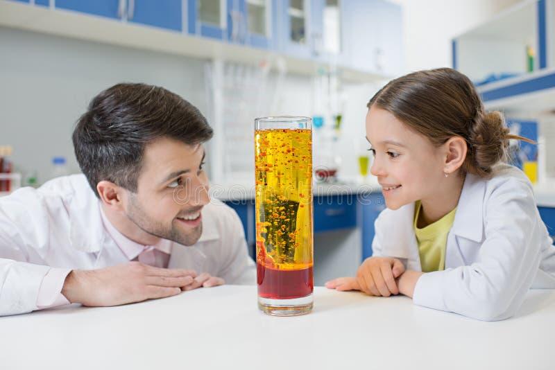 Portret uśmiechnięci mężczyzna dziewczyny i nauczyciela ucznia naukowowie patrzeje eksperymentalnej tubki obraz stock