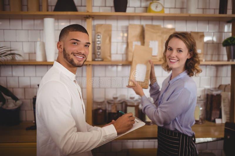 Portret uśmiechnięci męscy właściciela i kelnerki ułożenia pakunki na półce zdjęcie stock