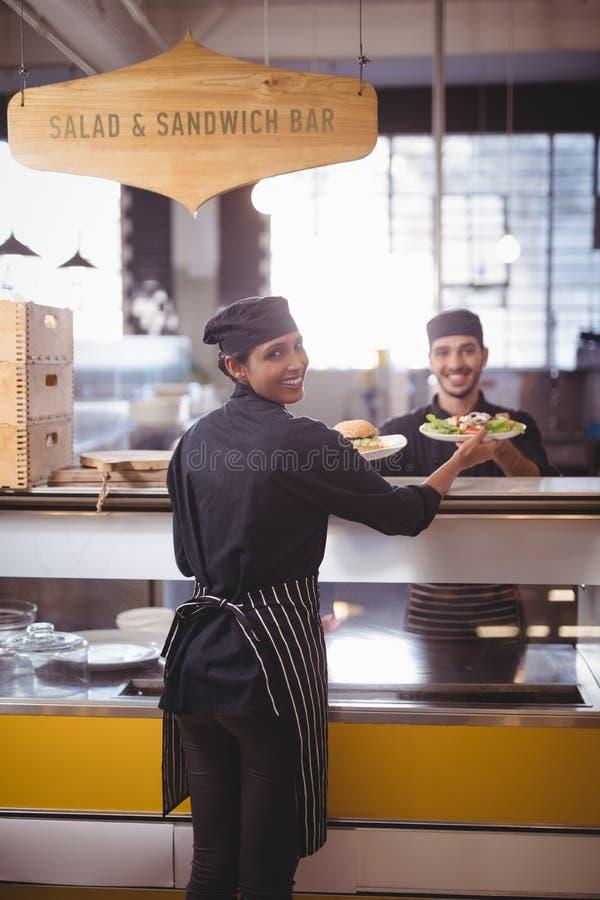 Portret uśmiechnięci młodzi kelnera i kelnerki mienia talerze przy kontuarem fotografia stock