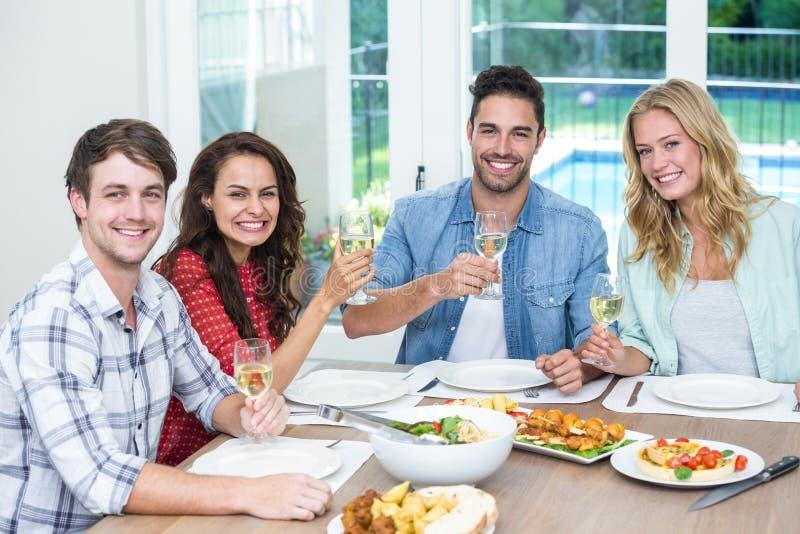 Portret uśmiechnięci przyjaciele trzyma win szkła obrazy royalty free