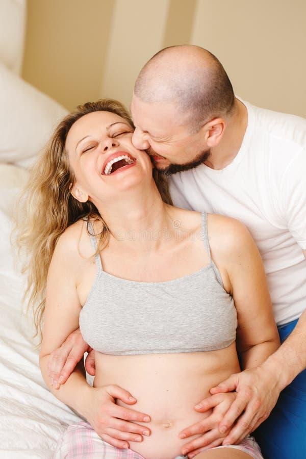 Portret uśmiechnięta śmia się biała Kaukaska młoda wiek średni para, kobieta w ciąży z mężem w pokoju na leżanki przytulenia cudd zdjęcie royalty free