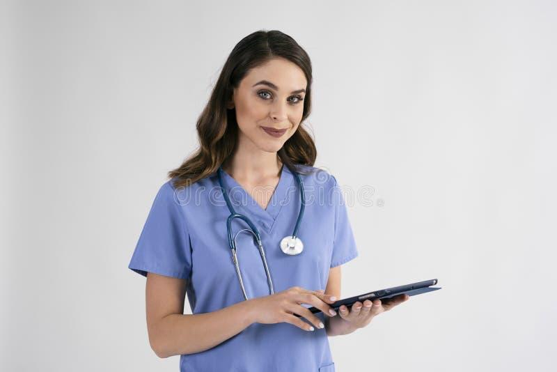 Portret uśmiechnięta żeńska pielęgniarka z pastylką i stetoskopem fotografia stock