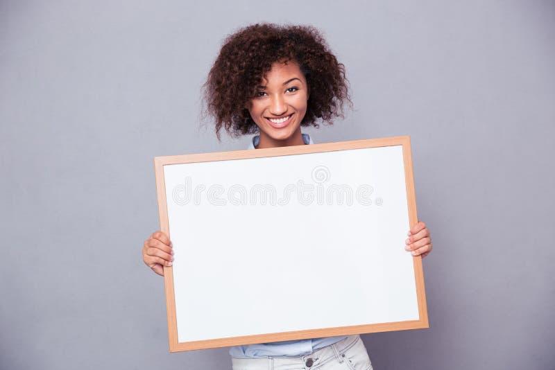 Portret uśmiechnięta afro amerykańska kobiety mienia pustego miejsca deska obraz stock