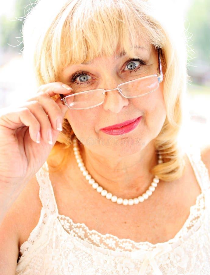 Portret uśmiechnięta atrakcyjna starsza dama w eleganckiej szacie z szkłami fotografia stock