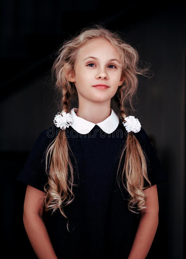 Portret uśmiechnięta blondynki siedem roczniaka dziewczyna w mundurku szkolnym zdjęcia stock
