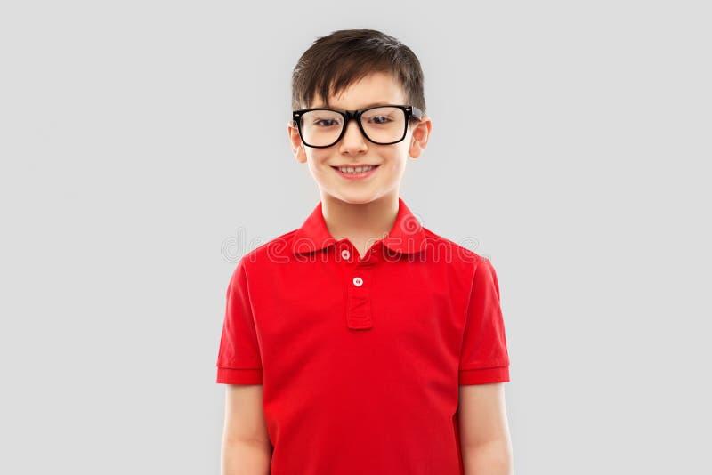 Portret uśmiechnięta chłopiec w szkłach i czerwonej koszulce zdjęcia stock