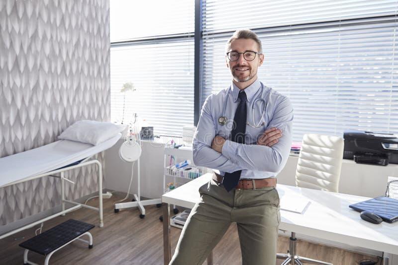 Portret Uśmiechnięta Dojrzała samiec lekarka Stoi Bezczynnie biurko W biurze Z stetoskopem zdjęcie stock