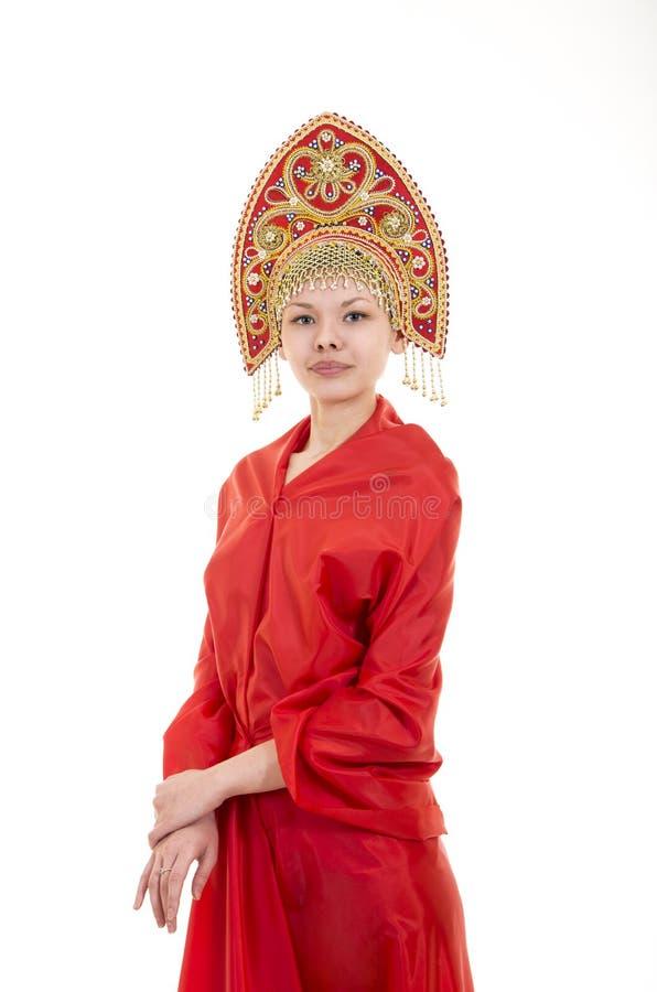 Portret uśmiechnięta dziewczyna w kokoshnik & x28; headdress& x29; i czerwieni suknia na białym tle zdjęcia stock