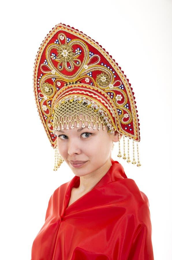 Portret uśmiechnięta dziewczyna w kokoshnik & x28; headdress& x29; i czerwieni suknia na białym tle obraz stock