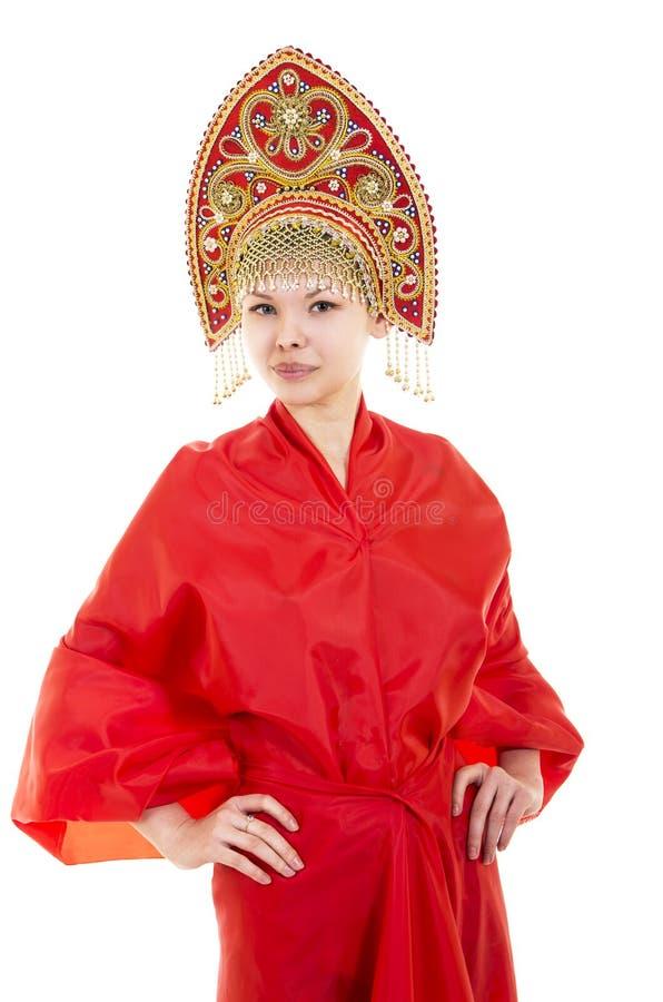Portret uśmiechnięta dziewczyna w kokoshnik & x28; headdress& x29; i czerwieni suknia na białym tle obrazy stock