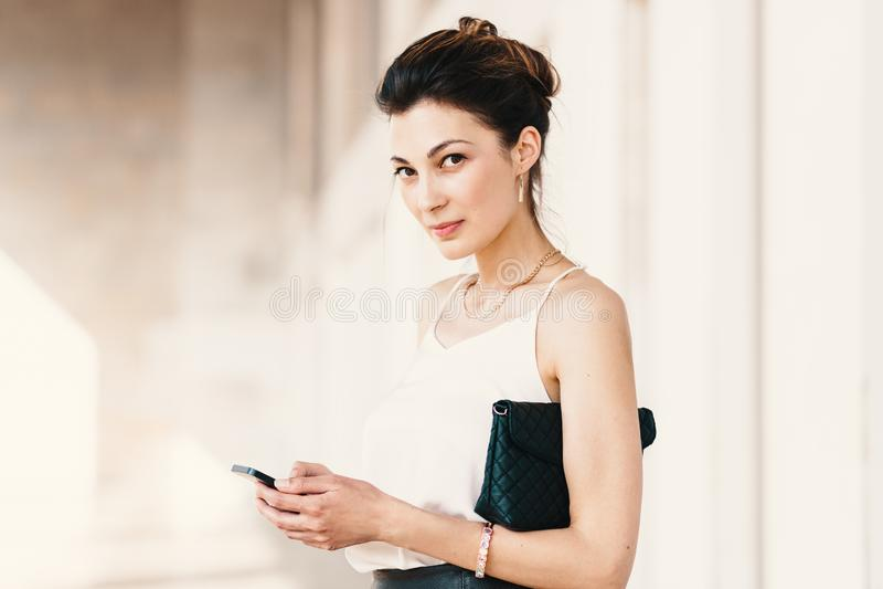 Portret uśmiechnięta elegancka młoda kobieta używa mądrze telefon zdjęcie stock