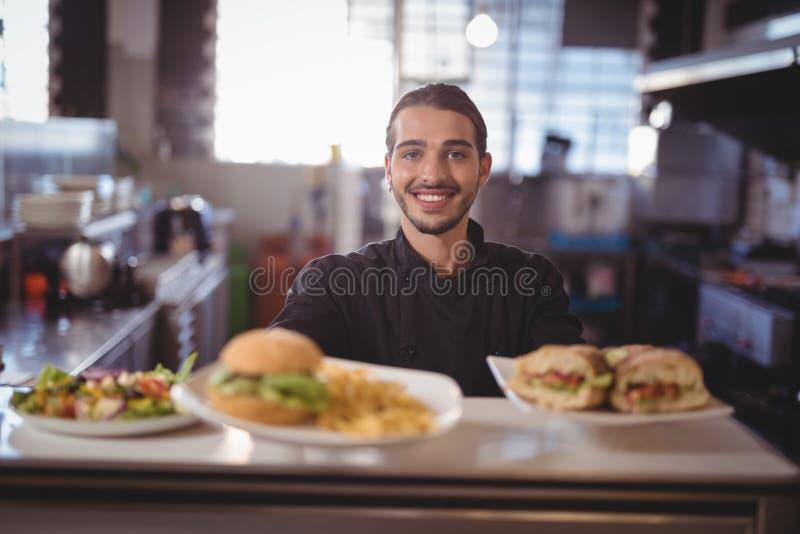 Portret uśmiechnięta kelner porci świeża żywność przy kontuarem obrazy stock