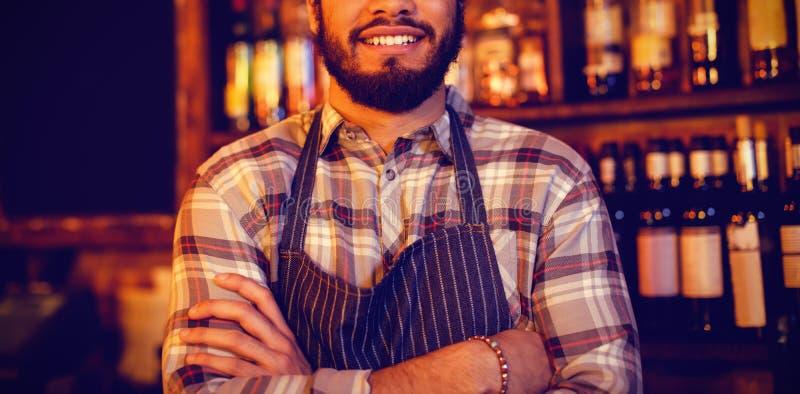 Portret uśmiechnięta kelner pozycja z rękami krzyżować zdjęcie royalty free