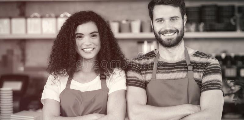 Portret uśmiechnięta kelnera i kelnerki pozycja przy kontuarem obrazy stock