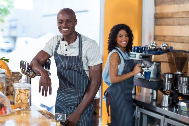 Portret uśmiechnięta kelnerka i kelner pracuje przy kontuarem fotografia stock