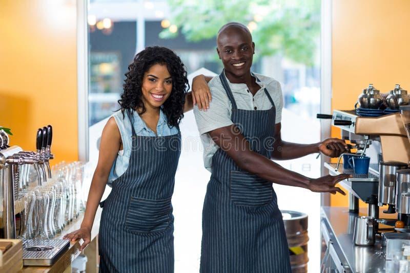 Portret uśmiechnięta kelnerka i kelner pracuje przy kontuarem zdjęcie royalty free