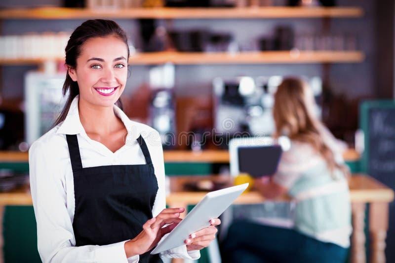 Portret uśmiechnięta kelnerka używa cyfrową pastylkę obraz stock