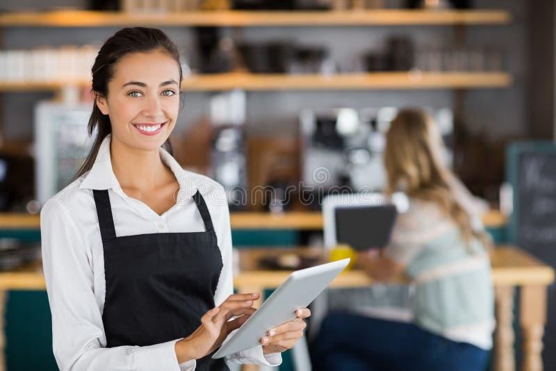 Portret uśmiechnięta kelnerka używa cyfrową pastylkę zdjęcie stock
