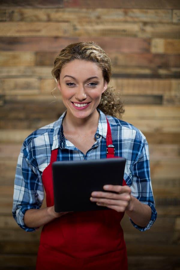 Portret uśmiechnięta kelnerka używa cyfrową pastylkę przeciw drewnianej ścianie obraz stock