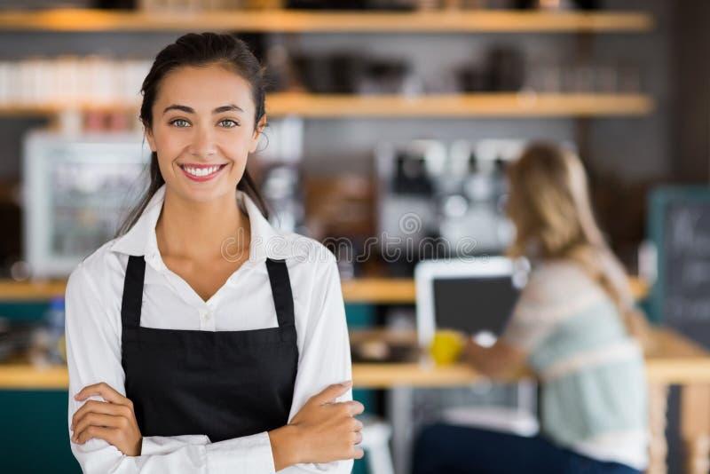 Portret uśmiechnięta kelnerki pozycja z rękami krzyżować obraz stock