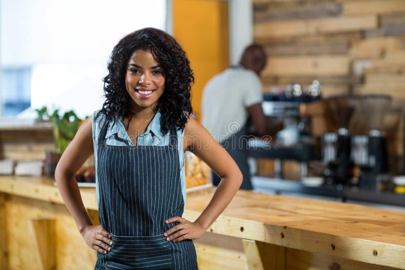 Portret uśmiechnięta kelnerki pozycja z rękami na biodrze przy kontuarem obraz royalty free