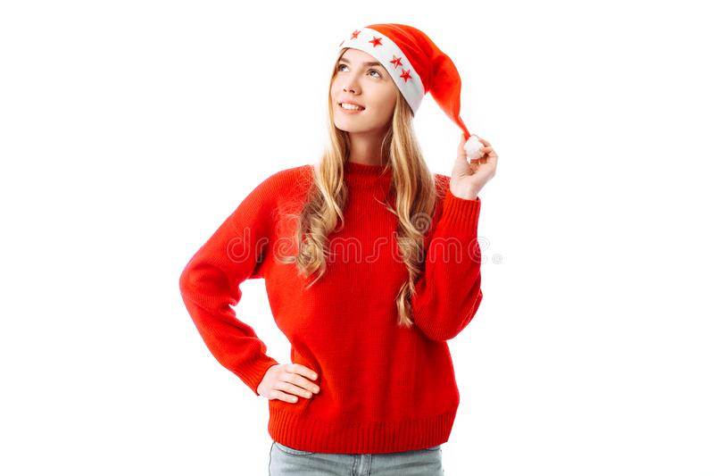 Portret uśmiechnięta kobieta jest ubranym i patrzeje strona pulower czerwonego Święty Mikołaj kapelusz i, pozycja, odizolowywając zdjęcia royalty free
