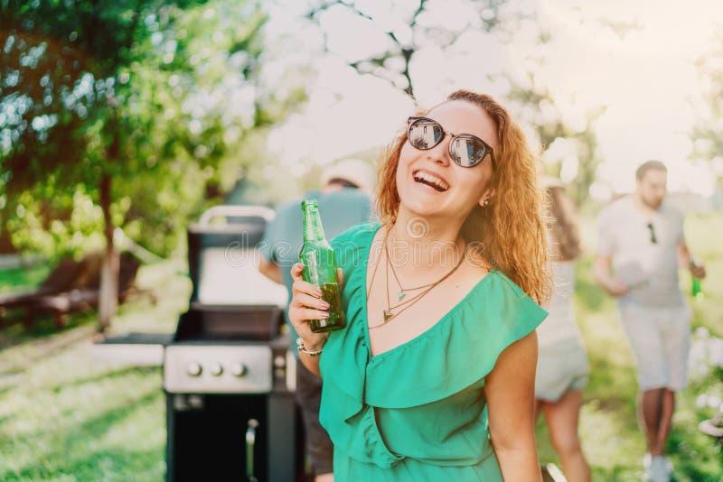 Portret uśmiechnięta kobieta ma napój z przyjaciółmi przy ogrodowym przyjęciem obrazy royalty free