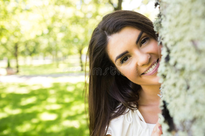 Portret uśmiechnięta kobieta za drzewnym bagażnikiem obraz stock