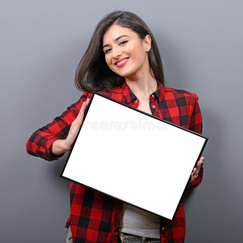 Portret uśmiechnięta kobiety mienia pustego miejsca znaka deska Pracowniany portret młoda kobieta z znak kartą przeciw szaremu tł zdjęcie stock