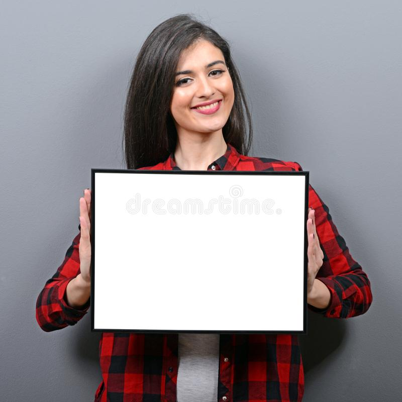 Portret uśmiechnięta kobiety mienia pustego miejsca znaka deska Pracowniany portret młoda kobieta z znak kartą przeciw szaremu tł obrazy stock